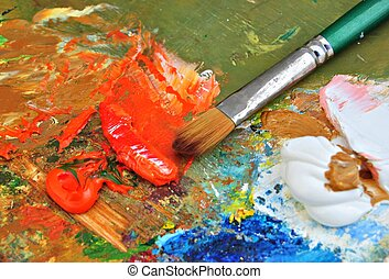 Palette of paints with oil paint, brush
