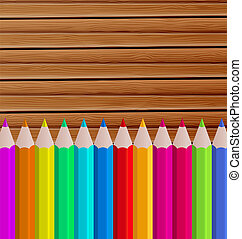 Palette pencils on wooden background