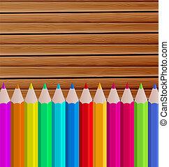 Palette pencils on wooden background