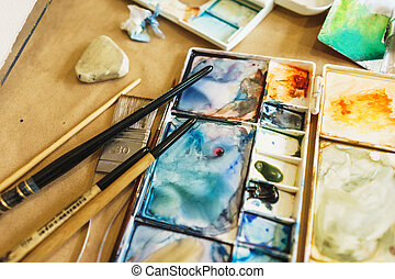 Palette with watercolors in different colors. Various brushes and pencils for drawing prepared by the artist for work.