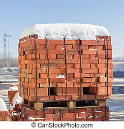 Pallets of the red bricks on a warehouse