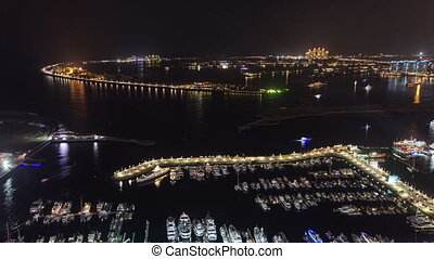 Palm Jumeirah with yahcts in harbor and Atlantis hotel at night general view from skyscraper Dubai marina timelapse