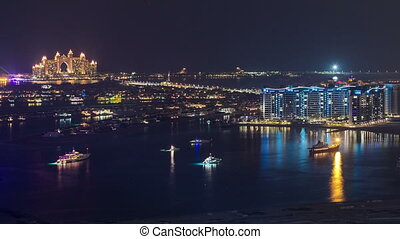 Palm Jumeirah with yahcts with Atlantis hotel at night view from skyscraper Dubai marina timelapse