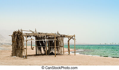 palm tree hut with garbage on the shores of the Red Sea in Egypt Dahab