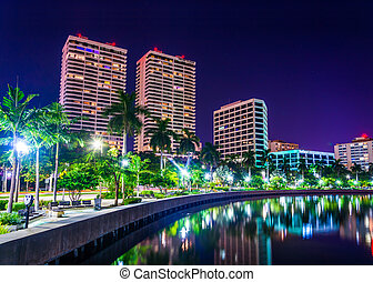 Palm trees along the Intracoastal Waterway and the skyline at night in West Palm Beach, Florida