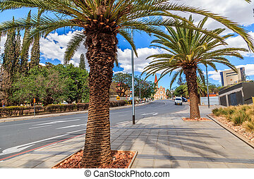 Palm trees along the  road and Luteran Christ Church in the end, central street of Windhoek, Namibia