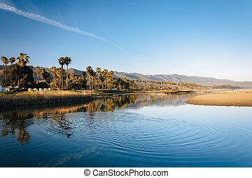 Palm trees and mountains reflecting in Mission Creek, in Santa Barbara, California.