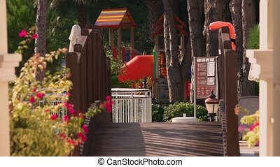 Palyground and walkway to kids club. Kids play area at tropical holiday resort. Summer vacation concept.
