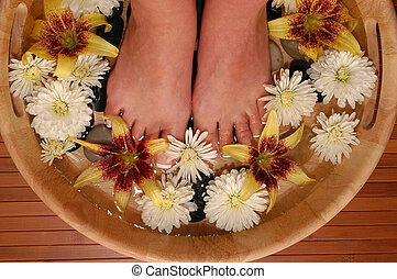 Pampered Feet - A pair of pedicured feet in a bowl full of...