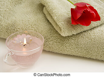 Pampering - Still life of towel, hand cloth, candle and red...