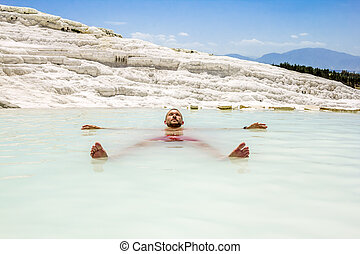 A man swims in the pool of thermal springs and travertine Pamukkale
