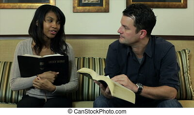 The camera pans from a lovely African American girl and a male friend to a woman engaging them in conversation about what they are studying in their Bibles.