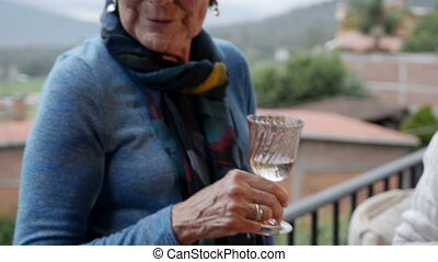 Pan down of senior women's hands holding drinks outside on a...