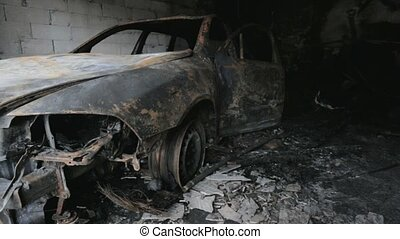 pan footage of burned out car in garage after fire, grunge...