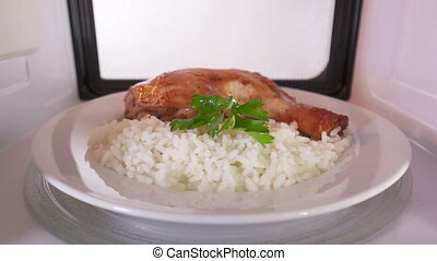 Pan fried chicken leg with rice on a plate reheating in the microwave