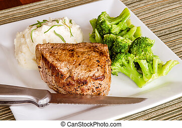 Pan-fried top sirloin filet steak with broccoli and mashed...