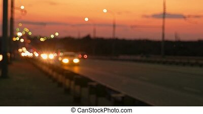 Pan left shot of defocused commuters cars in sunset time