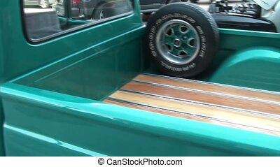 Panning a turquoise classic truck bed and finishing toward front along drivers side.
