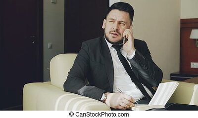 PAN of confident businessman talking mobile phone and writing notes in notepad while sits on armchair in hotel room. Travel, business and people concept