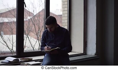Pan of young man studying sitting on the windowsill.
