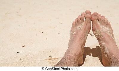 pan on feet in sand on sunny beach