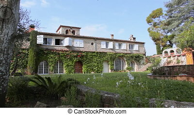 Pan over an Italian style villa and its garden with fountain