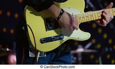 Pan playing electric guitar at concert