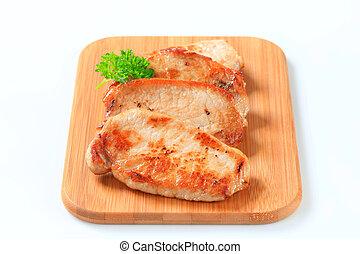 Pan seared pork cutlets on cutting board