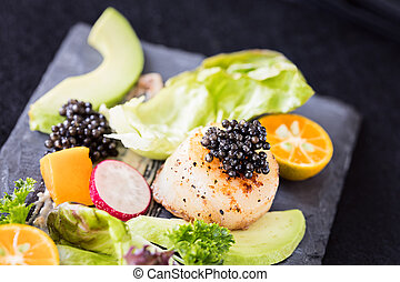 Pan seared scallops with salad, avocado, radish, mango and black caviar on a stone plate.