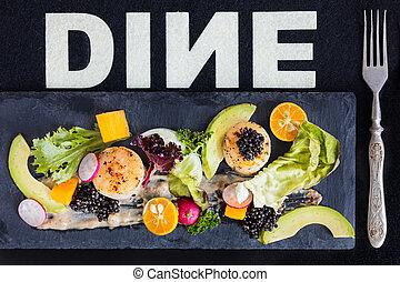 Pan seared scallops with salad, avocado, radish, mango and black caviar on a stone plate..1