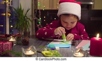 Little girl glues New Year card
