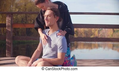 Woman massaging a man with a massage ball - Pan shot. Couple...