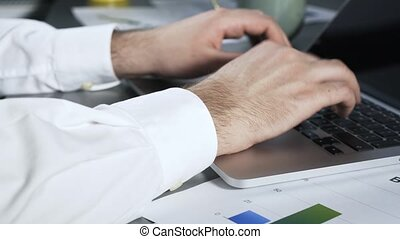 Pan shot of a businessman typing at laptop