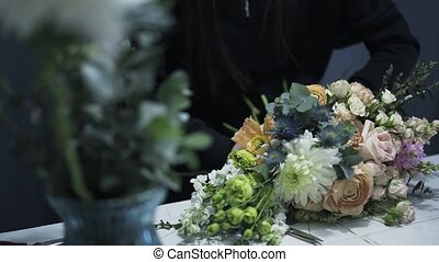 Pan shot of a florist shop assistant tying a bunch of flowers on a counter