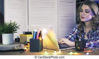 Pan shot of attractive young woman working on a laptop at casual office.