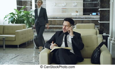 Pan shot of handsome bearded businessman sitting in armchair talking mobile phone with notepad while businesswoman with luggage walking through hotel lobby from reception desk