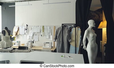 Pan shot of light clothing design studio with large tailor's...