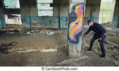 Pan shot of masked graffiti artist drawing abstract images on pillar in large empty building using paint spray. Painter is wearing casual clothing and protective gloves.