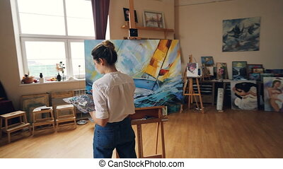 Pan shot of serious girl professional painter working in...