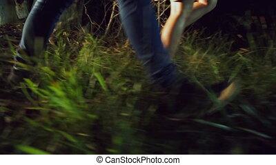 Pan shot of two people walking through forest at night