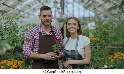 Pan shot of young smiling blogger couple gardeners in apron...