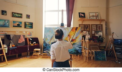 Pan shot of young woman focused on painting seascape on canvas in nice light studio standing near easel alone and working. Fine arts and people concept.