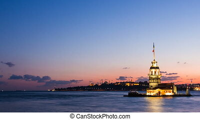 Pan shot timelapse of Maiden Tower or Kiz Kulesi with floating tourist boats on Bosphorus in Istanbul at night