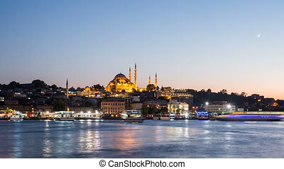Pan Timelapse view of Istanbul cityscape with Suleymaniye mosque with tourist ships floating at Bosphorus at night