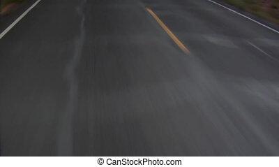 Pan up from highway to three bikers speeding