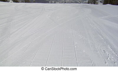 Pan up of groomed hill with mountainous vista
