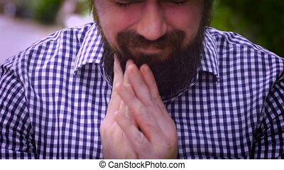 Pan up portrait of a bearded man looking up in desperation -...