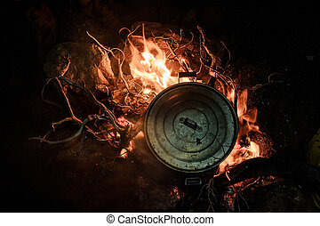 pan with a cover standing on the bonfire in the night