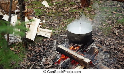 Pan with boiling soup over campfire in outdoor