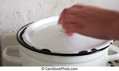 pan with broth where female hand prevents broth
